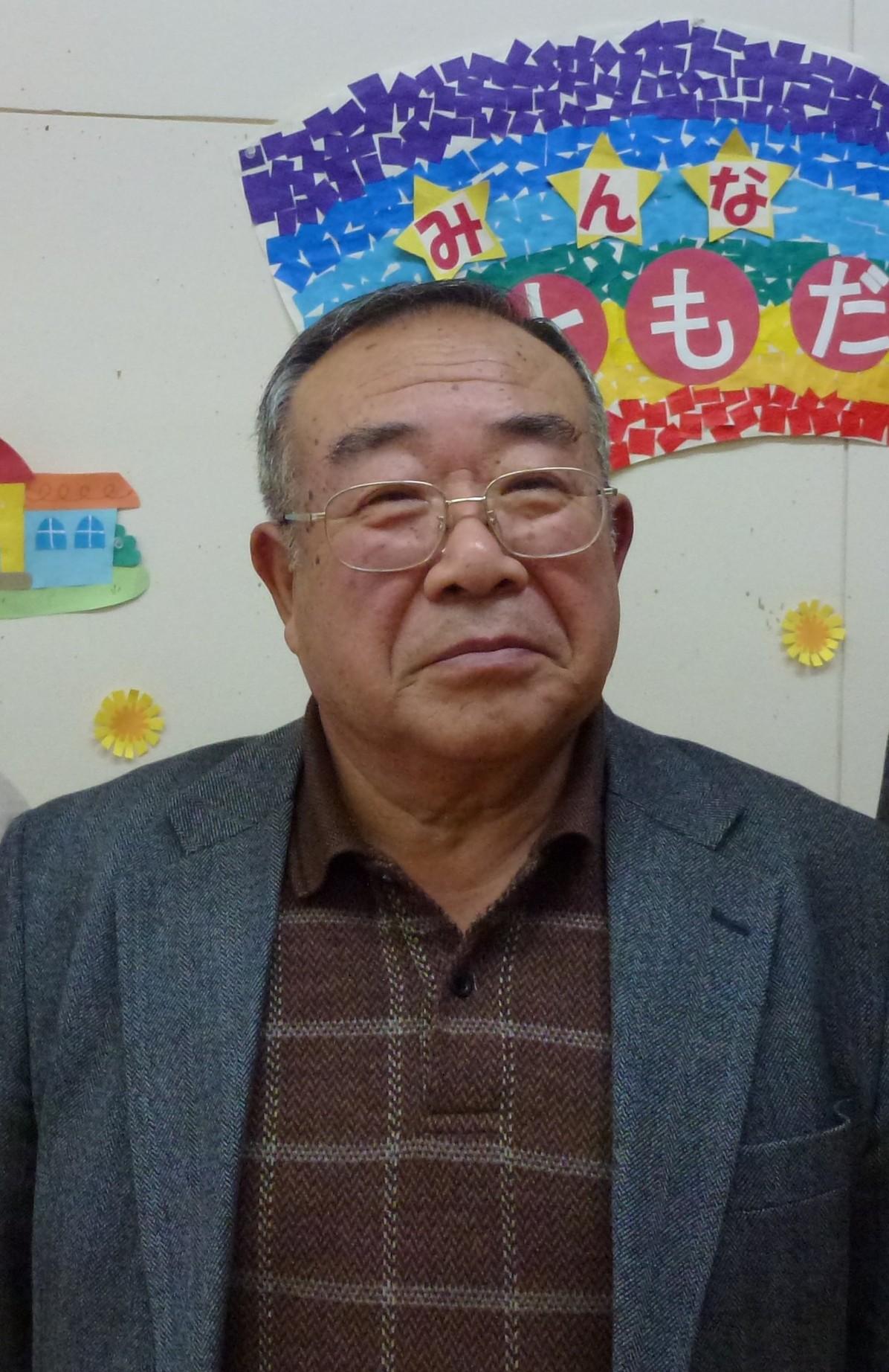 """Monsieur Tsuda. En arrière plan, une affichette proclame sur un fond d'arc en ciel: """"Tout le monde est notre ami"""""""